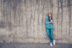 Natürliche Größe netter junger Dame, stehender naher Betonmauer ou lizenzfreies stockfoto