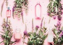 Natürliche kosmetische Produkte, die mit verschiedenen Flaschen und frische Kräuter und Blumen auf rosa Hintergrund, Draufsicht,  lizenzfreies stockbild