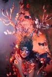 Natürliche Nymphe mit Hörnern wie Niederlassungen eines Baums und der Schmetterlinge, die herum einkreisen Fantasieartkostüm stockfotos