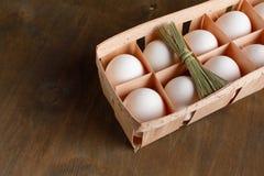 Natürliche organische Hühnereien im orange Papppaketisolat stockbilder