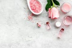 Natürliche organische Kosmetik mit rosafarbenem Öl Creme, Lotion, Badekurortsalz auf grauem copyspace Draufsicht des Hintergrunde stockfoto