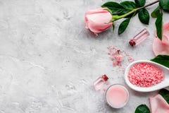 Natürliche organische Kosmetik mit rosafarbenem Öl Creme, Lotion, Badekurortsalz auf grauem copyspace Draufsicht des Hintergrunde lizenzfreies stockbild
