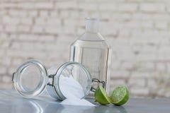 Natürliche Reinigungsprodukte, einschließlich Natriumbikarbonat, umgewandeltes Glas, Backnatron, Zitrone, Essig, auf grauer Tabel Lizenzfreies Stockbild