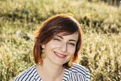 Natürliche reizende junge Frau, die in der Sommerwiese, Schönheit a aufwirft Stockfoto
