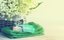 Natürliche Seife der Handarbeit, des Tuches und der Frühlingsblumen eines Maiglöckchens in einem geflochten Korb lizenzfreies stockbild