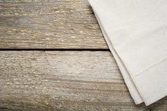 Natürlicher beige Baumwollstoff auf Holztisch Lizenzfreies Stockbild