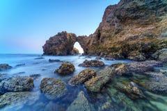 Natürlicher Felsenbogen, -klippe und -strand Stockbilder