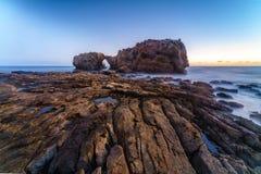 Natürlicher Felsenbogen, -klippe und -strand Stockfotografie