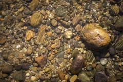 Natürlicher Konzepthintergrund des Flusssteins unter haarscharfem Wasser Stockfoto