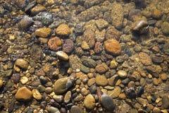 Natürlicher Konzepthintergrund des gelben Steins im klaren Flusswasser Lizenzfreie Stockbilder