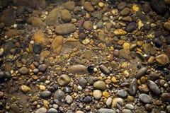 Natürlicher Konzepthintergrund des klaren Flusswassers und Stein setzen auf den Strand Stockbilder