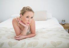 Natürliches aufwerfendes blondes Lügen auf Bett Stockfotos