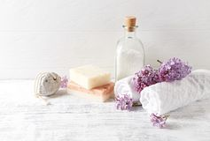 Natürliches Badesalz, Seife, Baumwolltücher und symbolisches Bild der Fliederblumen Stockfotografie