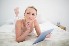 Natürliches durchdachtes blondes Lügen auf dem Bett, das Tablette hält Lizenzfreies Stockfoto