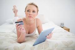 Natürliches durchdachtes blondes Lügen auf dem Bett, das Tablette und Kreditkarte hält Stockfotos