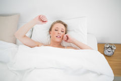 Natürliches gähnendes blondes Lügen im Bett mit geschlossenen Augen Stockbild