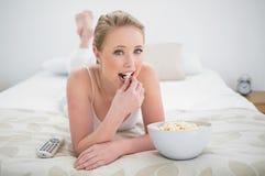Natürliches glückliches blondes Lügen auf Bett und Essen des Popcorns Lizenzfreie Stockbilder