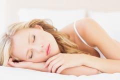 Natürliches junges blondes Lügen auf ihrem Bett schlafend Lizenzfreie Stockfotos