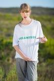 Natürliches junges blondes Zeigen auf ihr freiwillig erbietendes T-Shirt Stockfoto