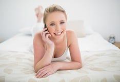 Natürliches lächelndes blondes Lügen auf Bett und Anrufen Stockfotografie