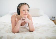 Natürliches lächelndes blondes Lügen auf Bett und Hören Musik Lizenzfreie Stockfotos