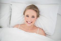 Natürliches lächelndes blondes Lügen im Bett Lizenzfreie Stockfotografie