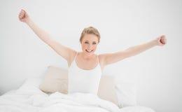 Natürliches lächelndes blondes Sitzen im Bett und Ausdehnen ihrer Arme Stockfoto
