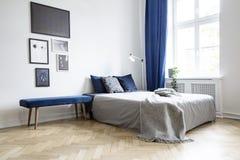 Natürliches Licht, das durch ein großes Fenster in einen Weiß- und Marineblauschlafzimmerinnenraum mit gemütlichem Bett und Brett lizenzfreie stockfotos