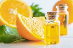 Natürliches Orangenöl in der Flasche und in der Schnittorangenfrucht auf weißem Holztisch lizenzfreies stockfoto