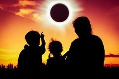 Natürliches Phänomen Silhouettieren Sie hintere Ansicht des Familiensitzens und des r Stockfoto