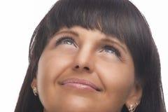 Natürliches Porträt der glücklichen Brunettefrau, die oben schaut Stockbilder