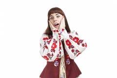 Natürliches Porträt der kaukasischer Brunette-weiblichen Aufstellung im nationalen blumigen Kleid Ausruf rührende Backen zeigen Lizenzfreies Stockbild