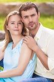 Natürliches Porträt von den jungen kaukasischen Paaren, die zusammen Outd sitzen Stockfoto