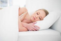 Natürliches recht blondes Schlafen im Bett Stockfotografie