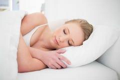Natürliches ruhiges blondes Schlafen im Bett Lizenzfreie Stockbilder