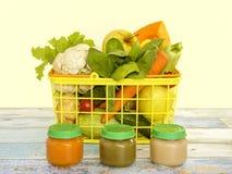 Natürliches Säuglingsnahrungskonzept: Gläser mit Gemüsepüree und Korb mit Gemüse auf dem hellen hölzernen Hintergrund Lizenzfreies Stockbild