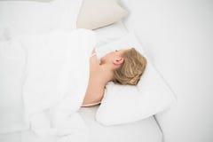 Natürliches schönes blondes Schlafen im Bett Lizenzfreie Stockfotos