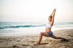 Natürliches schauendes übendes Yoga der schwangeren Frau an der Küste a Stockbilder