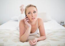 Natürliches skeptisches blondes Lügen auf Bett und Anwendung von Smartphone Lizenzfreies Stockbild