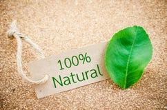 100% natürliches Wort bereiten an braunes Tag mit grünem Blatt auf Lizenzfreie Stockfotos