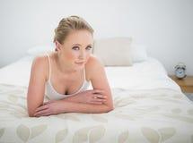 Natürliches zufriedenes blondes Lügen auf Bett Lizenzfreie Stockfotografie