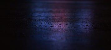 Nat asfalt, nachtsc?ne van een lege straat met wat bezinning in het water stock foto's