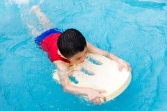Natação asiática de Little Boy do chinês com placa de flutuação Fotografia de Stock