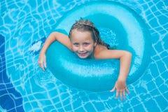 A natação bonita da menina na associação exterior e tem um divertimento férias Fotografia de Stock Royalty Free