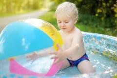 Natação bonito do rapaz pequeno em uma associação inflável fora no quintal no dia de verão ensolarado imagens de stock