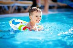 Natação bonito do rapaz pequeno na associação no anel de borracha, tendo o divertimento no aquapark, férias de verão felizes na p fotos de stock royalty free