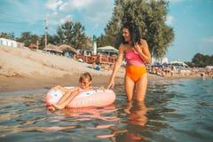 Natação da mamã e da filha em uma filhós inflável fotografia de stock