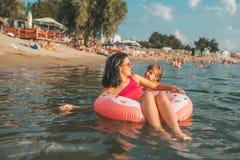 Natação da mamã e da filha em uma filhós inflável foto de stock