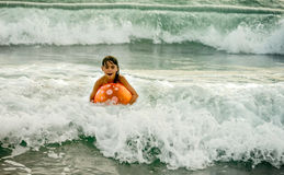 Natação da menina com a bola no oceano nas ondas Imagem de Stock