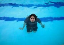 Natação da menina em uma associação com toda a roupa sobre Água azul bonita de turquesa fotografia de stock